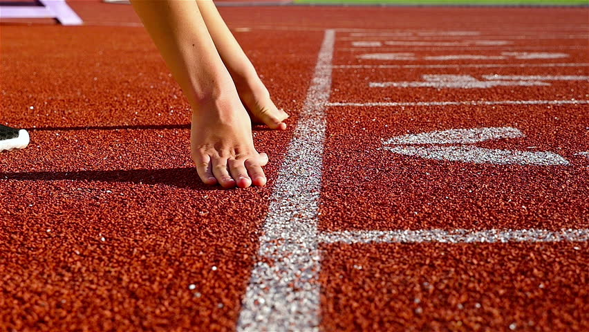 Track runner woman putting her hands at starting line, slow motion