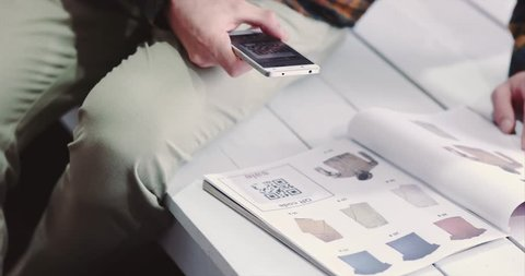 Man scanning qr code advertising with smartphone on clothes catalog modern technology and fashion shopping concept