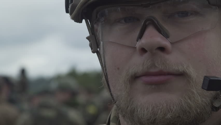 Portrait military man in  glasses,  army helmet and  walkie-talkie looking into camera. Face military soldier close up