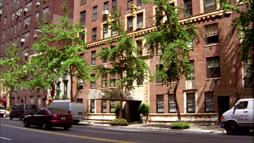 day Wide Pan right up from street entrance large Raked right eastern 10 14 story red brick apartment bldg 1 Bicycli street traffic thru