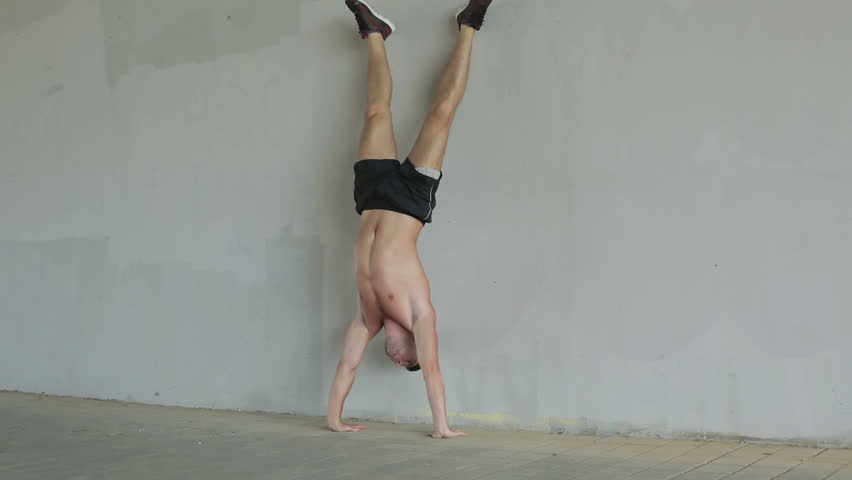 The young athlete is doing push-ups on hands standing upside down near the gray wall. Pushups in handstand. Young man topless in black shorts. Outdoor sports. Sports lifestyle. | Shutterstock HD Video #20523247