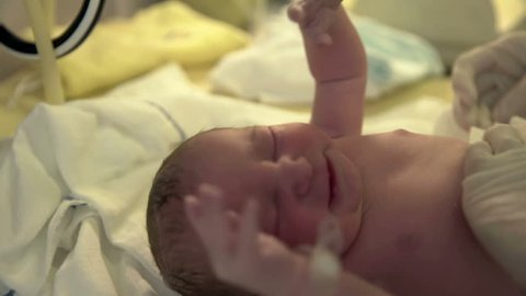 A nurse is putting a diaper on a new born baby. She is wearing gloves. A baby is crying a lot. Close-up shot.