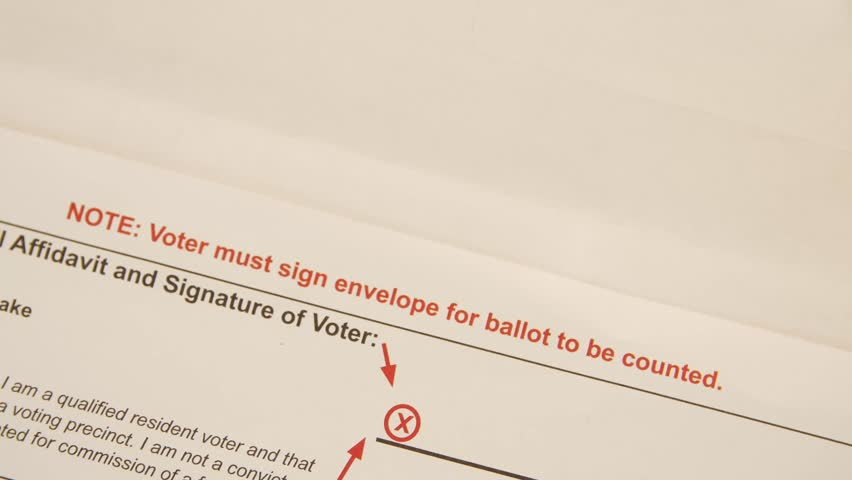 A Manu0027s Hands Slide A Mail In Ballot Into An Official Envelope For The 2016  Election