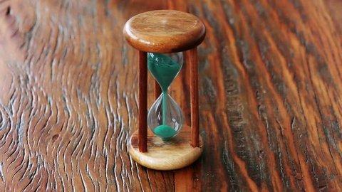 Green grains of an antique hourglass falls down. Cinemagraph technique.