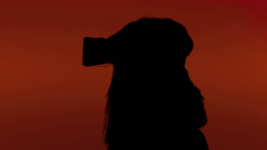 A woman putting on a virtual reality headset. Silhouette shot, red background.