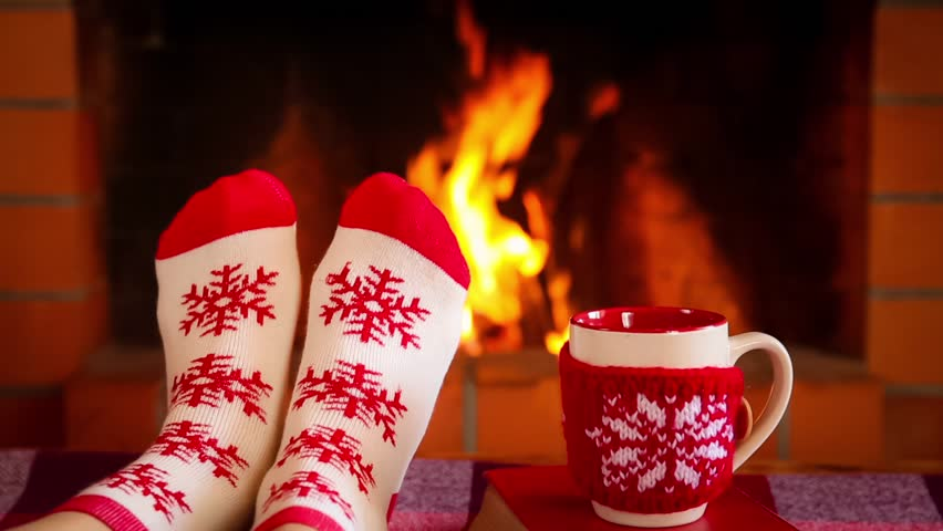 Girl in Christmas socks near fireplace. Woman relaxing at home. Winter holiday Xmas and New Year concept