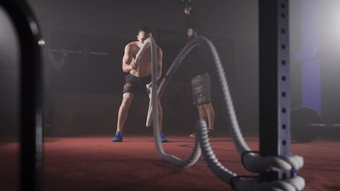 Sportsman doing heavy rope training at the gym.
