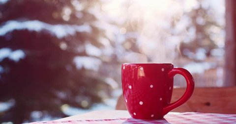 Steaming Cup of Hot Coffee or Tea standing on the Outdoor Table in Snowy Winter Morning. 4K DCi SLOW MOTION 120 fps. Cozy Festive Red Mug with a Warm Drink in Winter Garden. Christmas Morning Concept