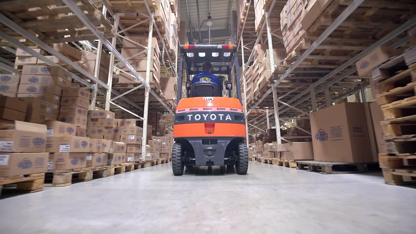 LUBLIN, POLAND - APRIL 21, 2016: Forklift Trucks Move Between Large Metal Shelves at a Modern Warehouse and Unload Pallets with Cardboard Boxes. | Shutterstock HD Video #20643277