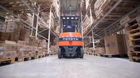 LUBLIN, POLAND - APRIL 21, 2016: Forklift Trucks Move Between Large Metal Shelves at a Modern Warehouse and Unload Pallets with Cardboard Boxes.