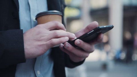 Businessman with small paper disposable cup of takeaway coffee using smartphones touch screen. Close up view of arms tapping it. Man texting on his mobile phone with a cup of coffee in a his hand