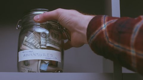 RL DOLLY Caucasian male putting a glass jar with his savings for future travels. 4K UHD RAW edited footage