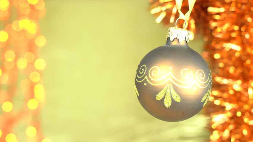 Christmas background in style of a xmas video greeting card, beautiful brown bauble hanging in front of golden bokeh lights and gold garland, room for Happy New Year, Best Wishes text. Loopable clip.