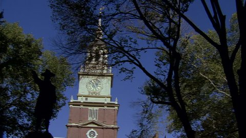 day Up Angle Pan left clock Philadelphia Independence Hall John Barry statue thru trees