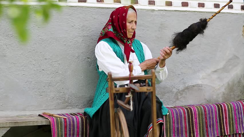 Elderly woman sits on bench and works with distaff with spinning wheel. Ukrainian old woman sits on bench near his house and spin yarn. Female with spinning wheel, handicraft | Shutterstock HD Video #20756317