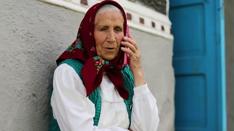 Old woman sits on bench near his house and speaks on cell phone. Ukrainian old woman with red smartphone. Female with smartphone