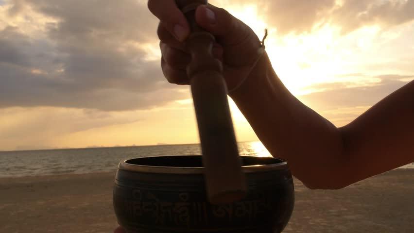 Meditation with Singing Bowl at Beach at Sunset