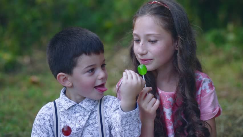 Beautiful little children eat lollipop candy in the garden.