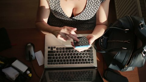 Busty sexy business woman working for a laptop. top view