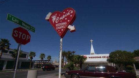 day tight Cupids Wedding Chapel sign Las Vegas Blvd street sign left, see chapel font color red Requires Clearance font