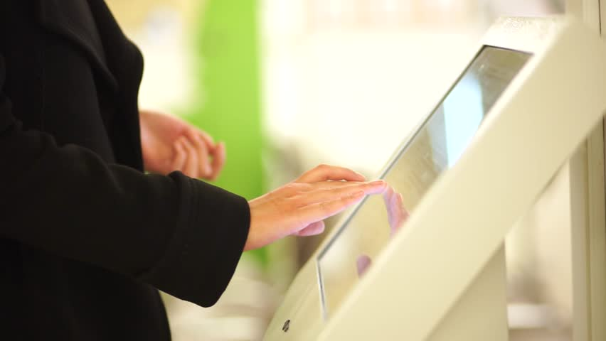 In the autumn dressed in dark coat, woman using the self services terminal to pay on the fare. Average plan.