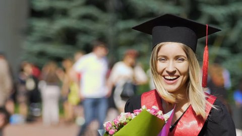 Happy female graduate laughing with bouquet of flowers in hands, celebration day. Excited girl student enjoying receiving university diploma graduation ceremony, slow motion. Achievement and success