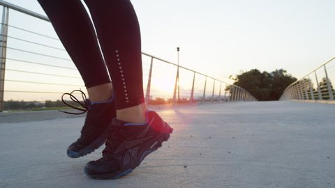 SLOW MOTION, CLOSE UP, LOW ANGLE VIEW: Active athletic girl doing leg worm up exercises on concrete bridge in green park at sunrise. Young female runner warming up and low skipping before running