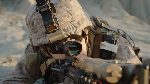 Close-up of Soldier Lies Down on the Hill, Aims through the Assault Rifle Scope in Desert Environment. Slow Motion. Shot on RED EPIC Cinema Camera in 4K (UHD).