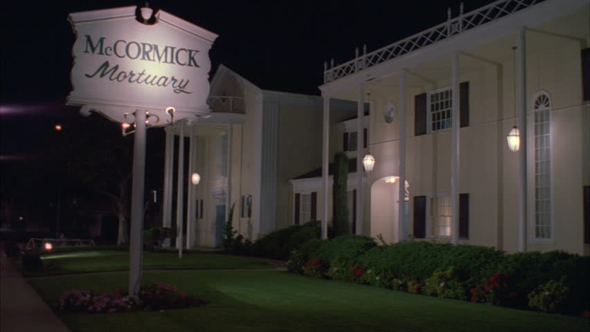 night raked right elegant yellow colonial style wood building with pillars, lit sign McCormick Mortuary funeral home