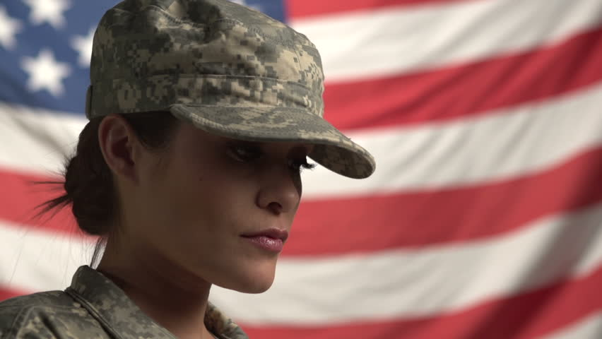 Female Soldier in front of flag, looking up