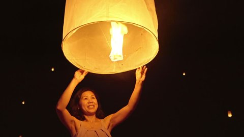 Asian woman releasing a sky lantern to wish for good luck.