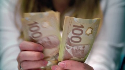 View of a woman Counting Many Canadian 100 bills, polymer plastic type, Woman not happy about not having enough money