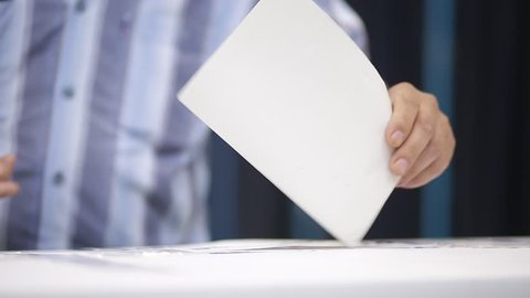 Unrecognizable people cast their vote during elections in a voting station.