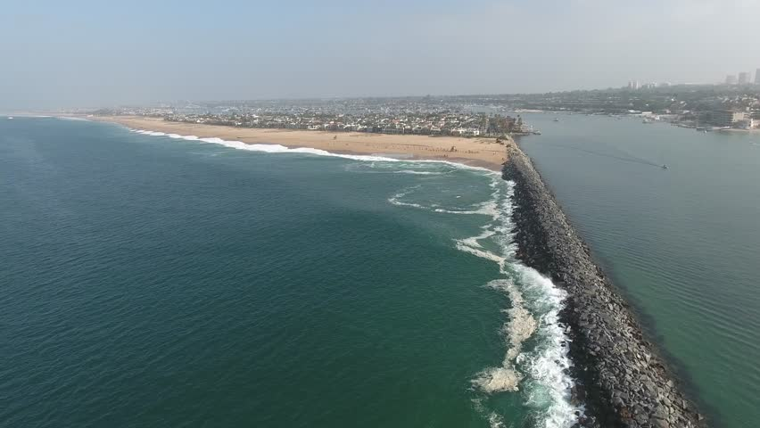 Aerial video above the Newport Beach jetty moving toward the world famous wedge, famous for surfers and body boarders.