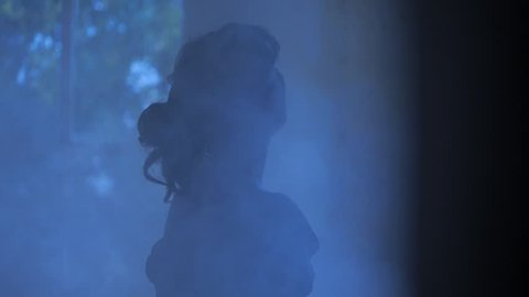 VIRGINIA - SUMMER 2016 - Reenactment, Recreation -- Ghostly, undead woman in smoky room in haunted house.  Paranormal, poltergeist.  Mystery woman with pale pallor, 19th century clothing in darkness