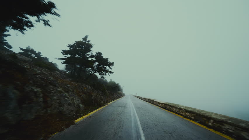 Pov driving on foggy dark scary mountain road at winter.Stabilized gimbal pov wide angle driving plate shot of a car driving through a mountain forest road at winter in fog and mis