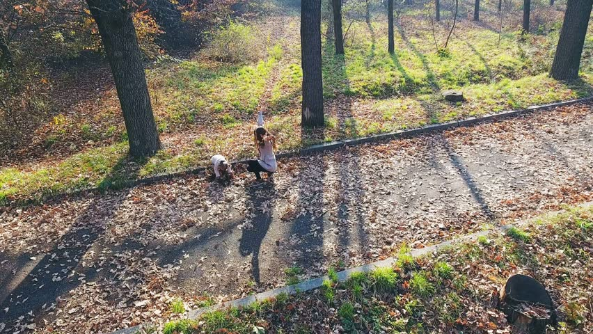 Mother with baby playing outdoor. Top view, dron helicopter. Autumn