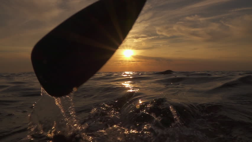SLOW MOTION, CLOSE UP: Female paddler pushing and pulling paddle blade by hands through crystal clear ocean water at magical golden sunset on relaxing summer vacation. Girl standup paddleboarding
