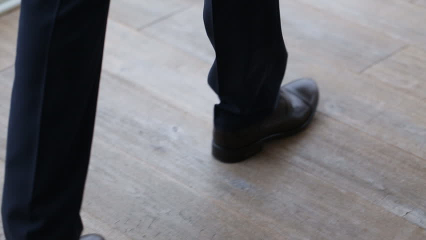 Close up of businessmen legs in black shoes and trousers walking on the floor