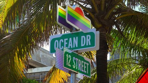 Rainbow commemorative LGBT street sign on a corner 12 street and Ocean Drive in Miami Beach, Florida.