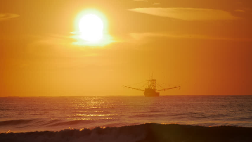Cinematic shot of shrimp boat at sunrise fishing waters of Atlantic Ocean off coast of South Carolina at Isle of Palms Just east of Charleston with waves in foreground and bright sun in background.
