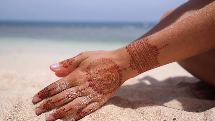 Sand Through Fingers on Beach. Hands with Henna Tattoo