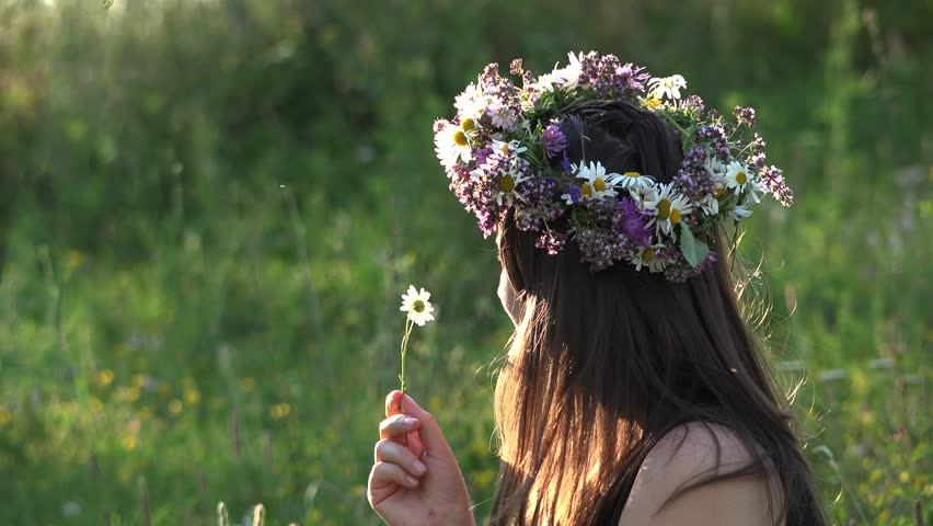 Woman with flower crown on her head playing with a daisy flower in a sunny day