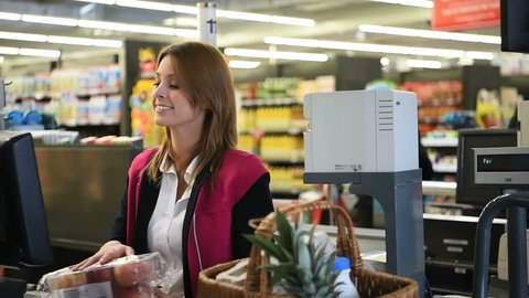Woman cashier scanning products at grocery store cash desk