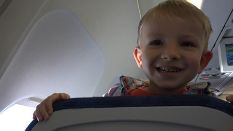 Happy child face appearing behind the chair in airplane, play hide and seek