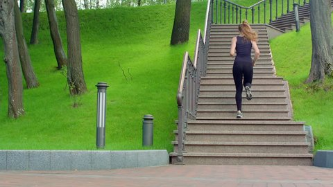 Woman running up stairs in slow motion. Real women run upstairs in park. Fit girl running up staircase at park. Lifestyle concept. Young woman fitness workout outdoor