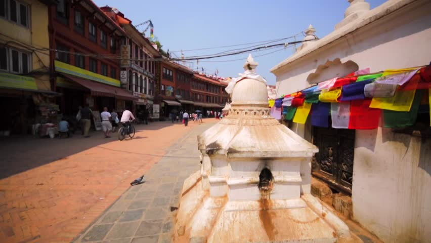 KATHMANDU, NEPAL - APRIL 11, 2016: Walking along colourful prayer flags of the Boudhanath stupa. View of the prayer whheel and white lingam. It's one of most popular tourist sites in Kathmandu area