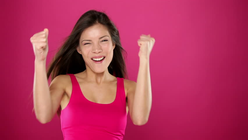 Excited winner woman celebrating winning something. Very happy ecstatic woman jumping and screaming of joy. Beautiful young mixed race Asian / Caucasian female model on pink background.