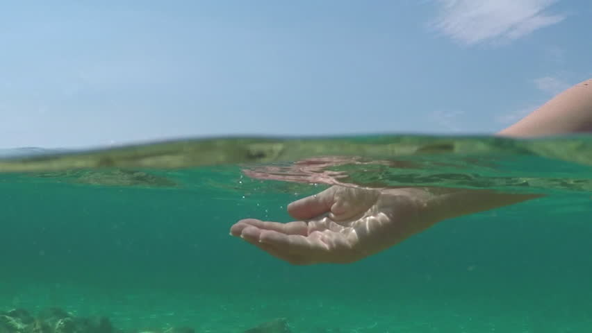 SLOW MOTION CLOSE UP HALF UNDERWATER: Caucasian female hand playing with water, catching it with fingers and pouring into the sea. Sun reflecting on waves and ocean surface on amazing sunny summer day #21148564