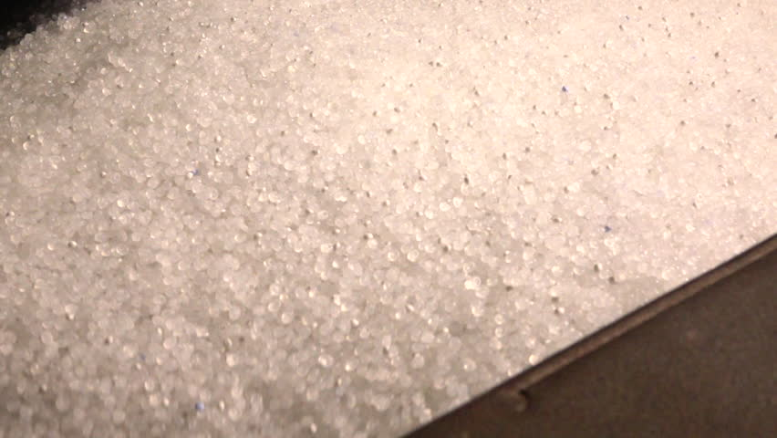 Plastic granules in container of the extrusion equipment. Shot in slow motion